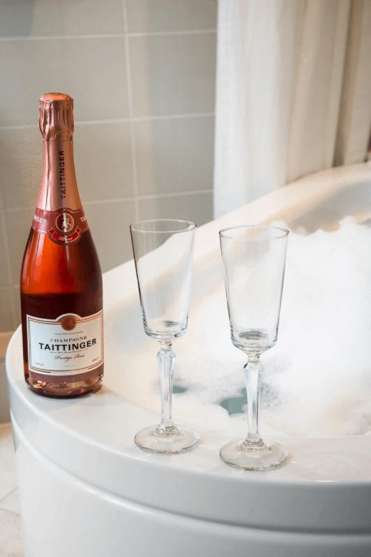 Baignoire et bouteille de champagne rosé sur le bord d'une baignoire dans chambre d'hôtel