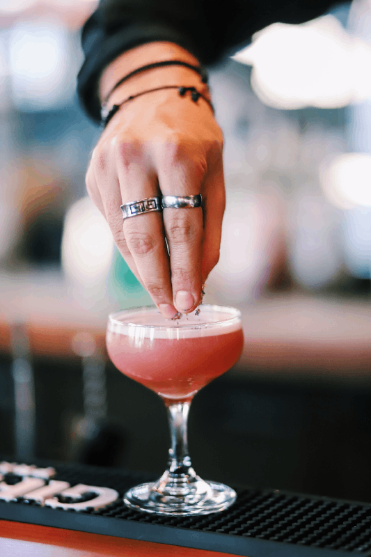 Cocktail rose avec main qui dépose des épices dessus