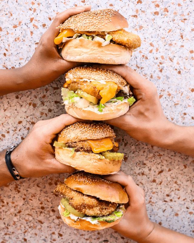 4 burgers empilés tenus chacun par une main différente